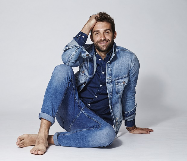 Barefoot dude in jeans smiling at camera
